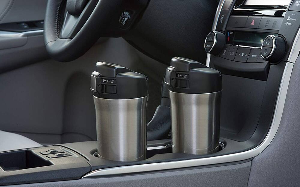 two stainless steel travel mugs in car holders