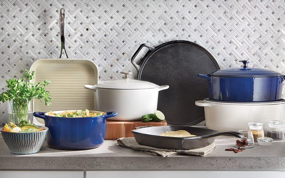 A cast iron skillet and griddle displayed with an assortment of other pots and pans