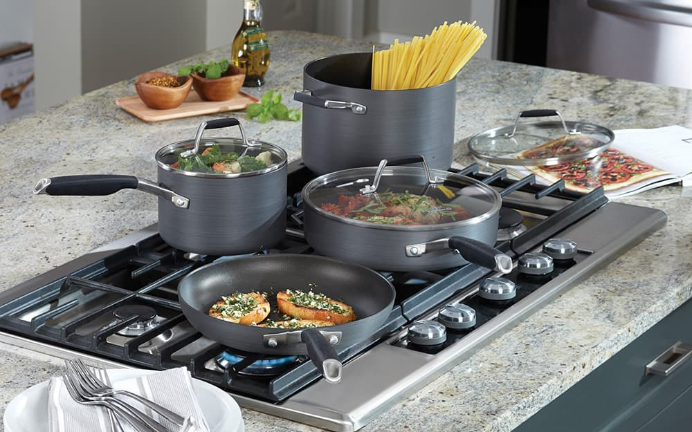 A cookware set with two pots, a skillet and a stock pot being used to cook pasta, vegetables and other foods on a stovetop