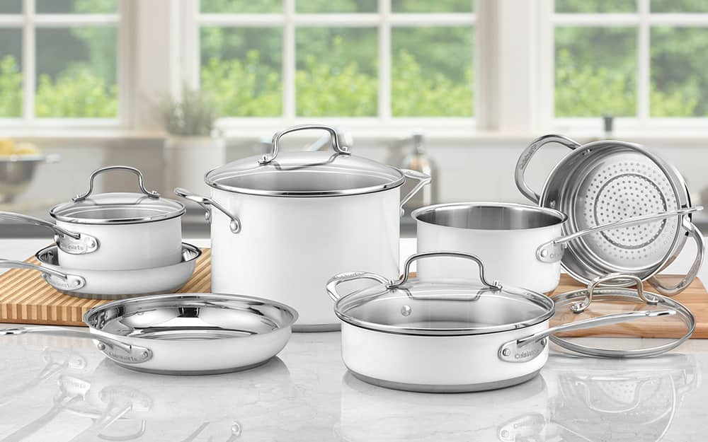A white cookware set with lids on a kitchen counter