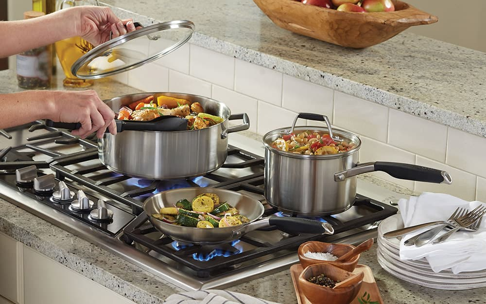 Food in a stainless steel cookware set on a stovetop