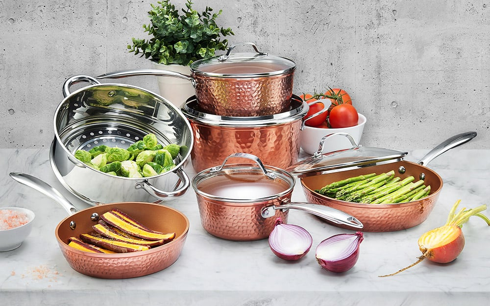 A copper cookware set of pots and pans with different foods in them