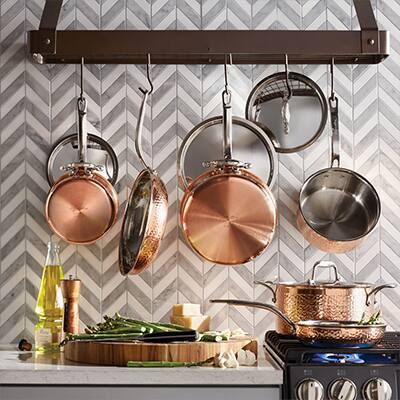 Copper pots and pans hanging from a wall-mounted rack