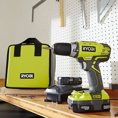 A cordless drill sits on a shelf with a charging battery and carrying case.