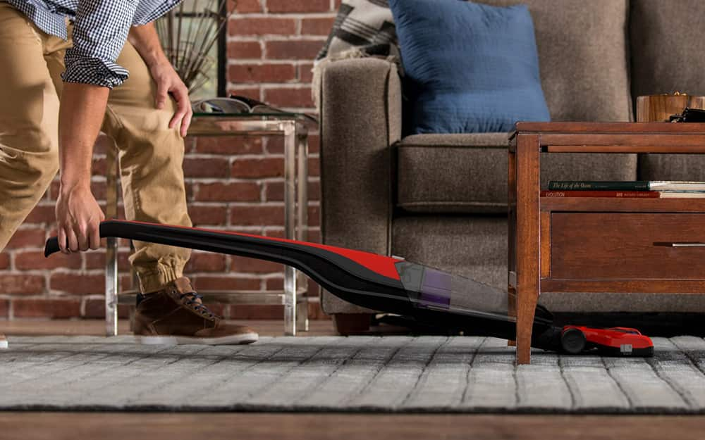 A person pushing a cordless vacuum on a rug under a table