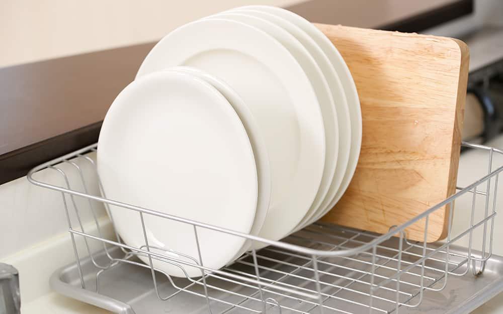 A cutting board drying in a dish rack.