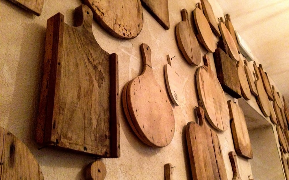 An assortment of cutting boards arranged on a wall.