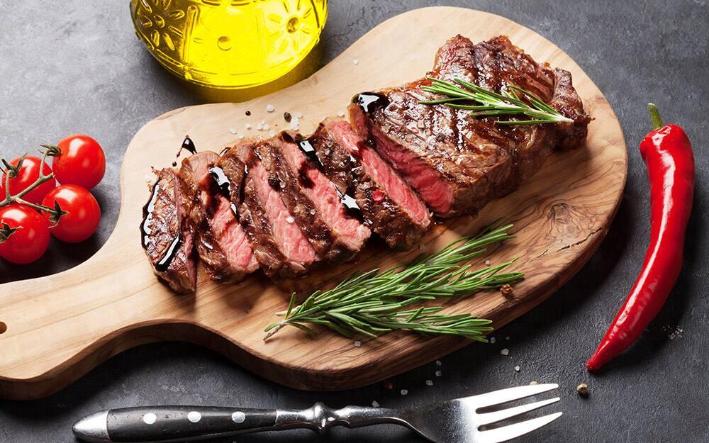 A wood cutting board with a sliced medium steak.