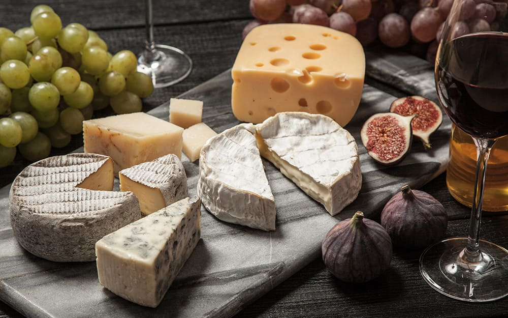 A marble cutting board with assorted cheeses and fruits arranged on top.