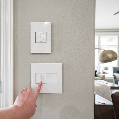 A person adjusts a dimmer switch.