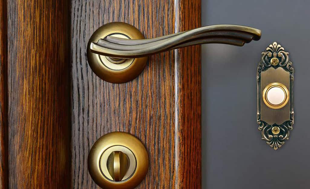An ornate wired doorbell next to a front door handle.