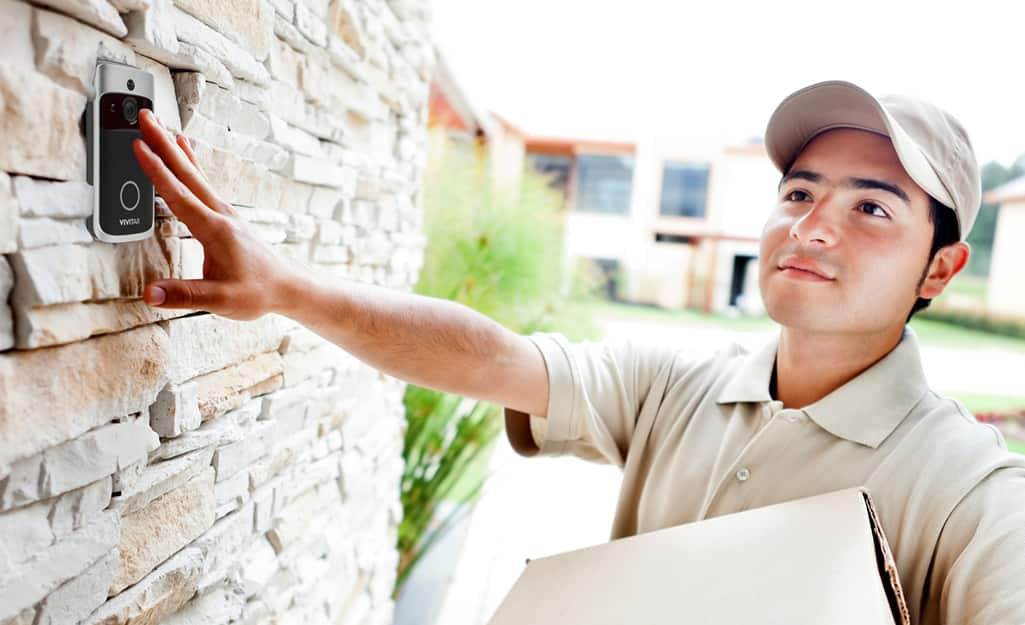 A delivery person ringing a smart doorbell.