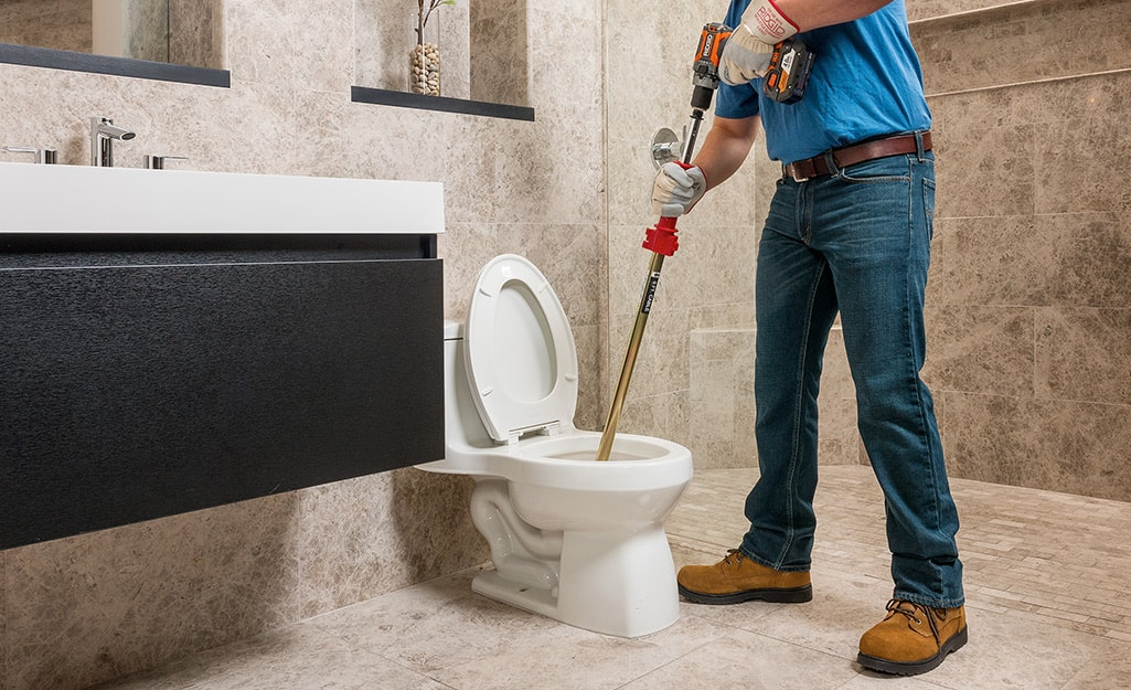 A person using an auger in a toilet