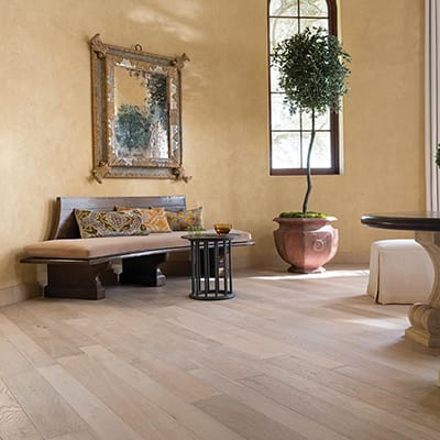 A Mediterranean style room with light engineered wood flooring.