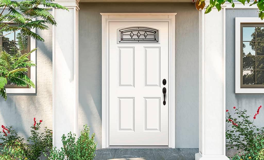 A prehung exterior door on a gray house.