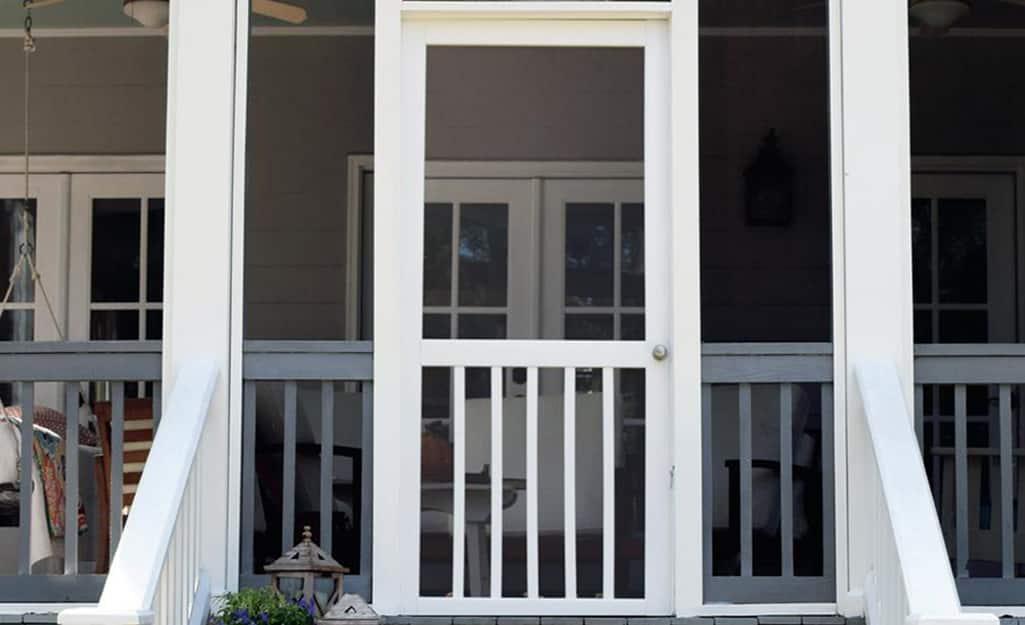 A white screen door as an entrance to a porch.
