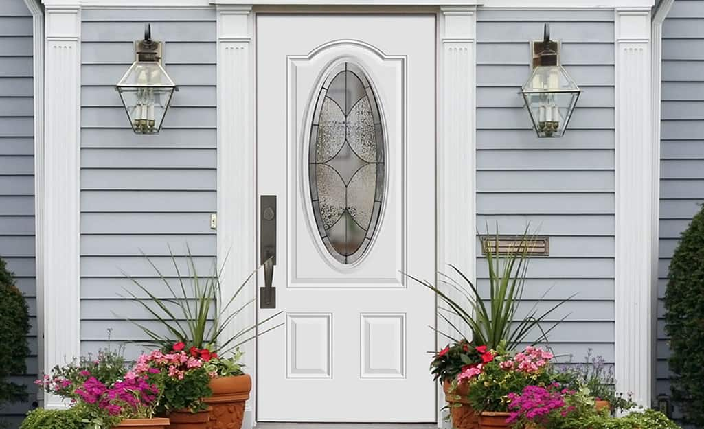 A steel exterior door surrounded by gray siding.