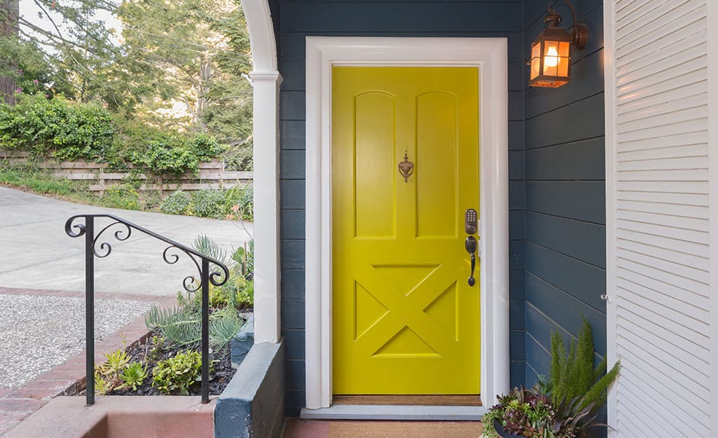 A front door painted yellow with a high-gloss finish.
