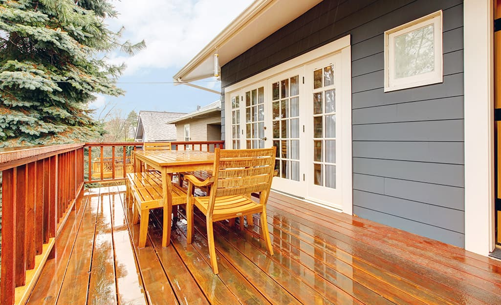 A rainfall leaves wet deck boards on a back deck.