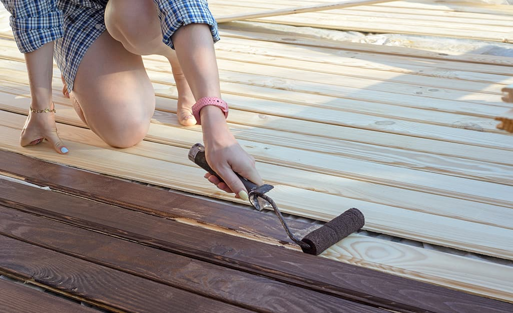 A person applies wood stain to a deck.