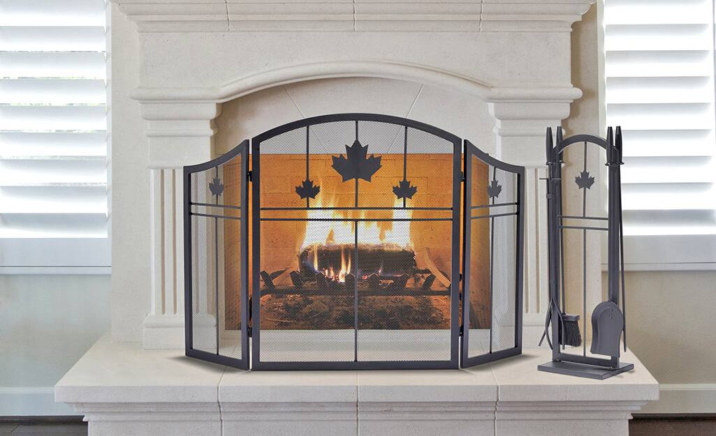 A fireplace screen in front of a lit fireplace.