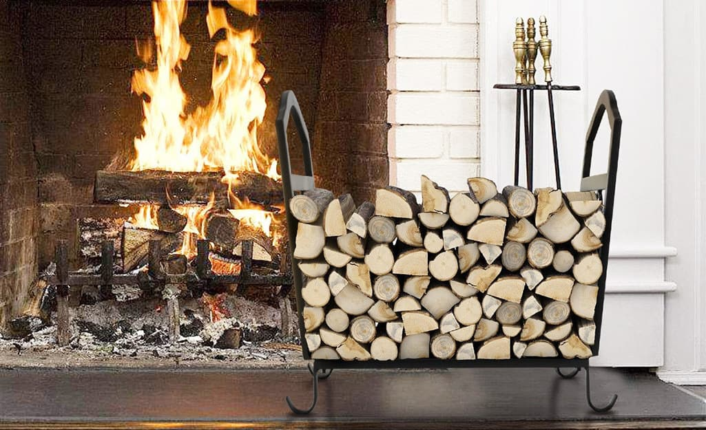 Wood stacked in a wood rack next to a roaring fireplace.