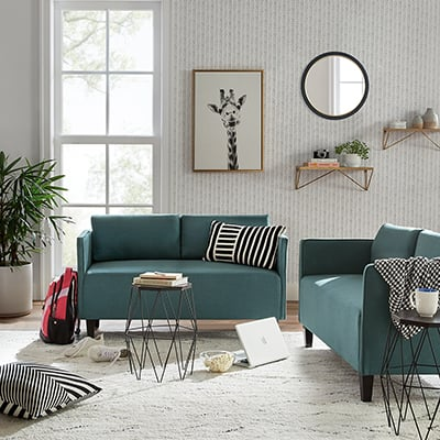 A living room with green sofa and love seat and modern decor.