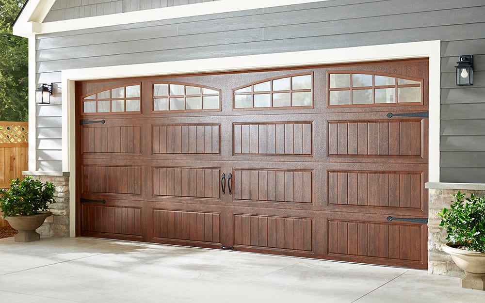 A wooden garage door with windows.