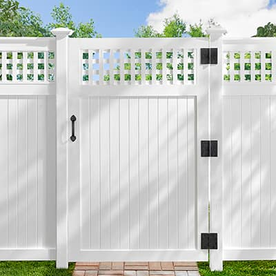 A white fence and gate with black gate hardware.