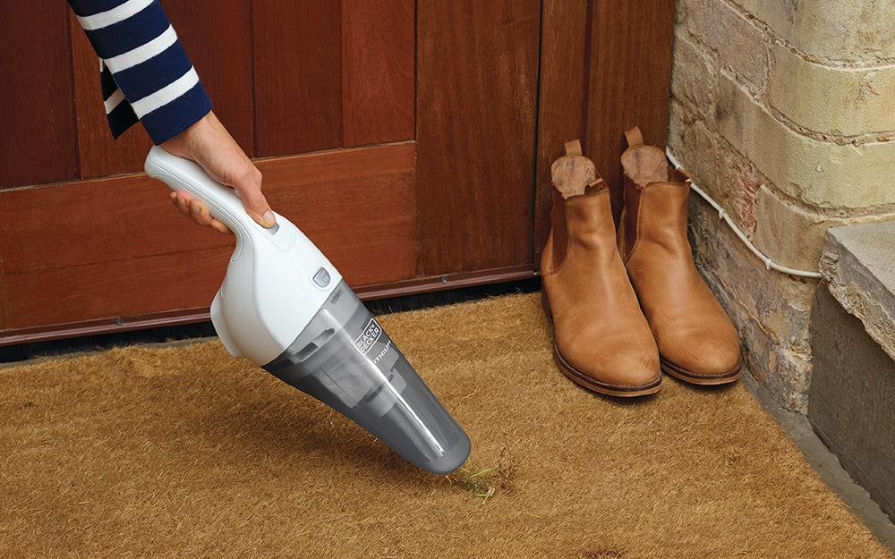 cleaning dirt off floor with handheld vacuum