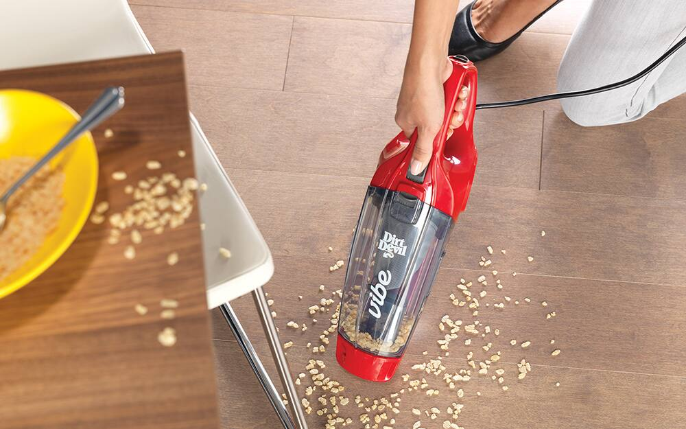 cleaning crumbs off hardwood floor with handheld vacuum