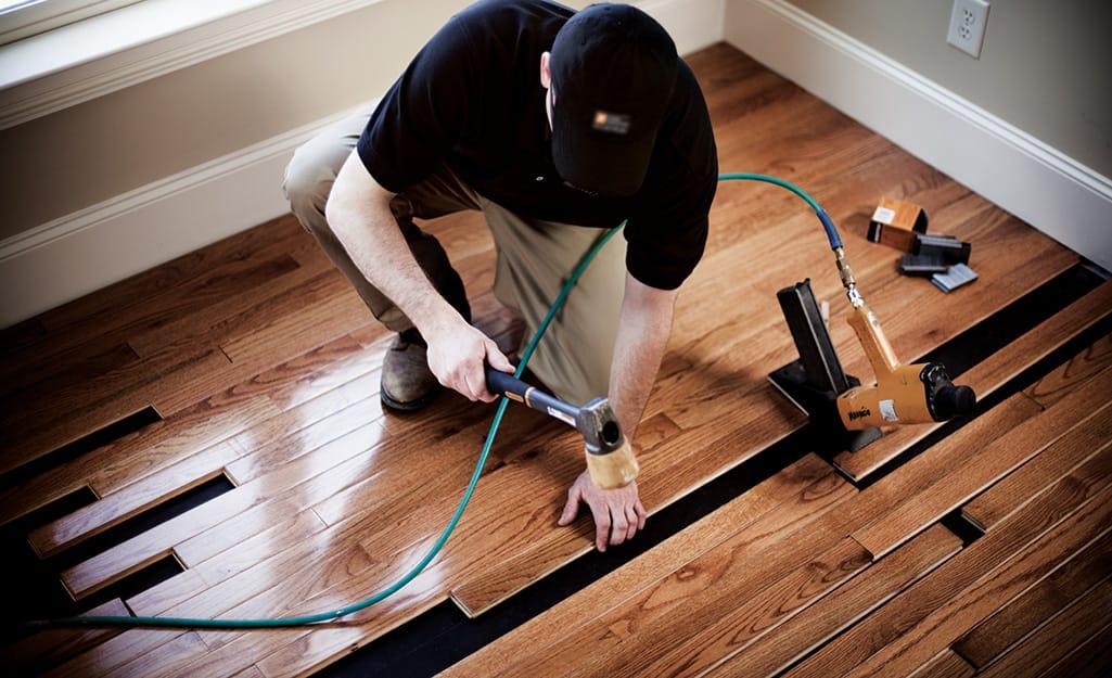 A flooring installer works on hardwood floors.
