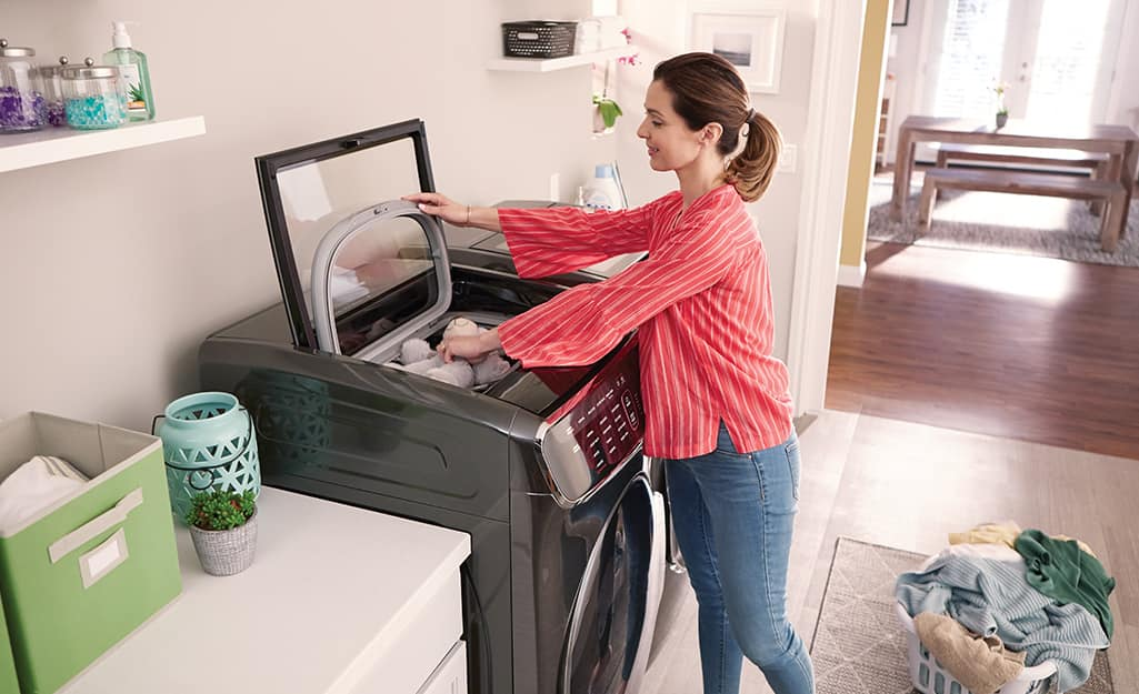 A woman putting laundry into a top-load high-efficiency washing machine.