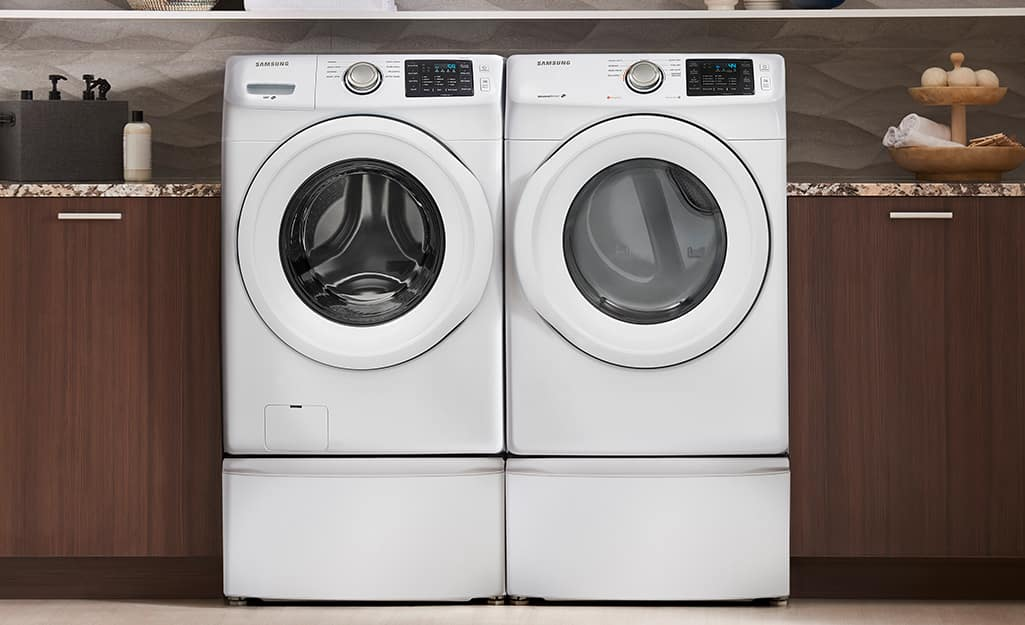 A front-load high efficiency washing machine sitting next to a front-load dryer.
