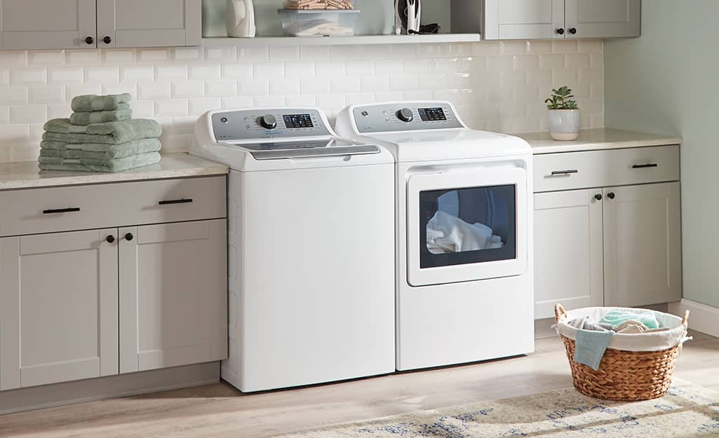 A white high-efficiency washer and dryer sitting side-by-side in a laundry room.
