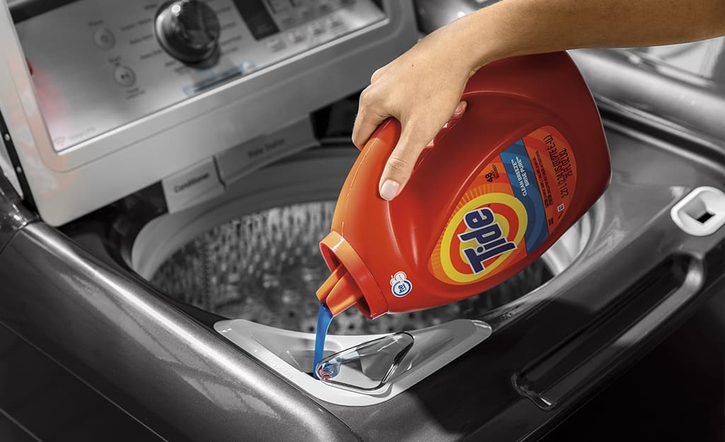 Someone pouring high-efficiency laundry detergent into a high-efficiency washing machine.