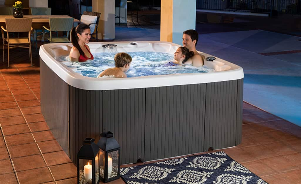A family enjoying a hot tub on the patio.
