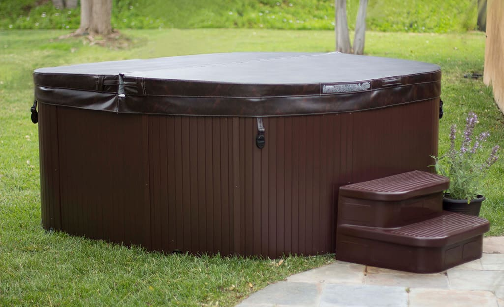 An outdoor hot tub covered with a protective top.