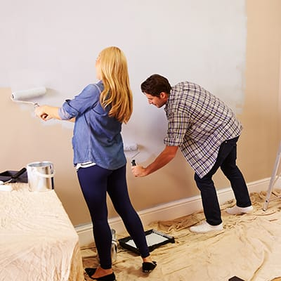 Couple painting a wall with rollers.
