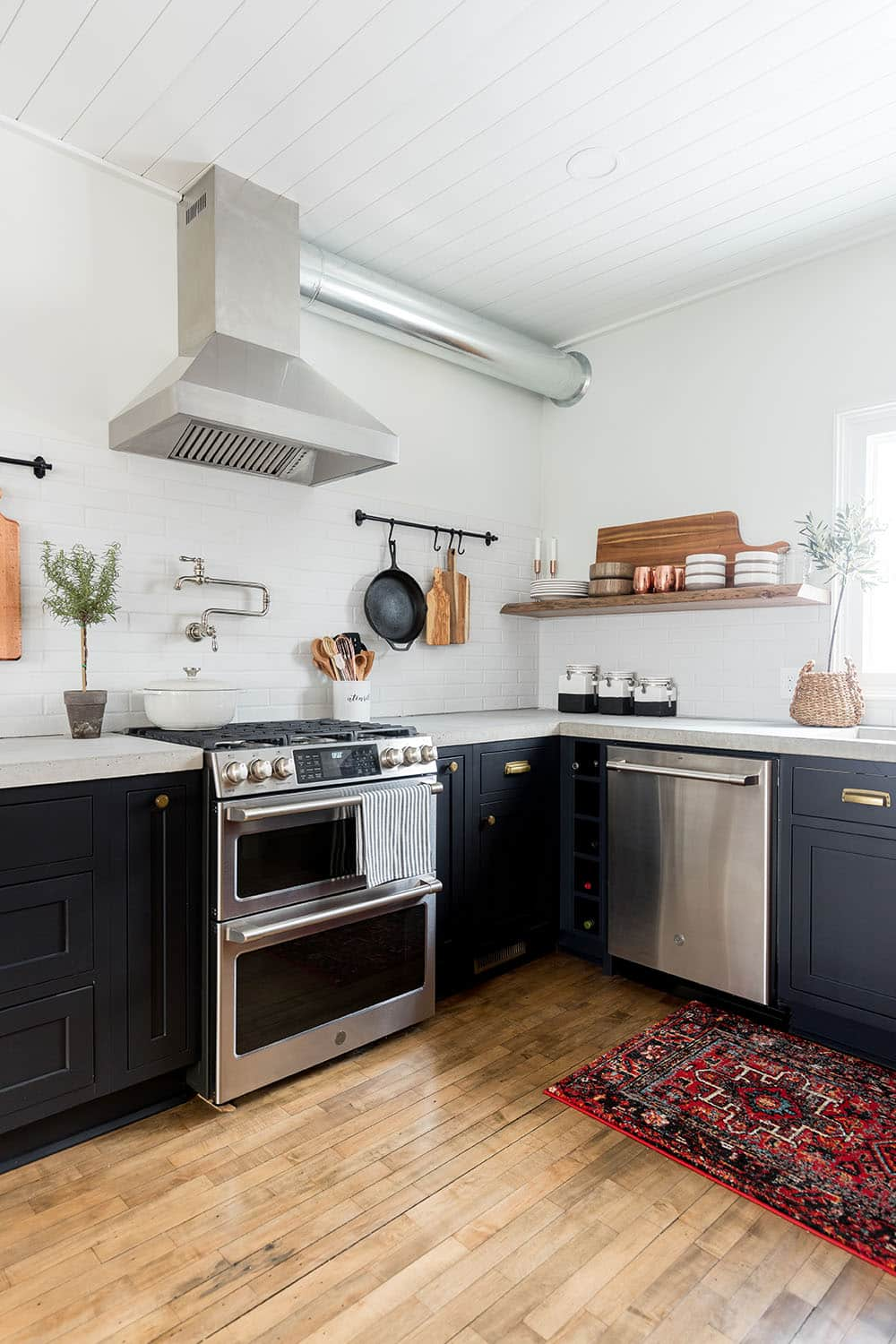 The corner of a kitchen with GE Cafe stainless steel appliances.