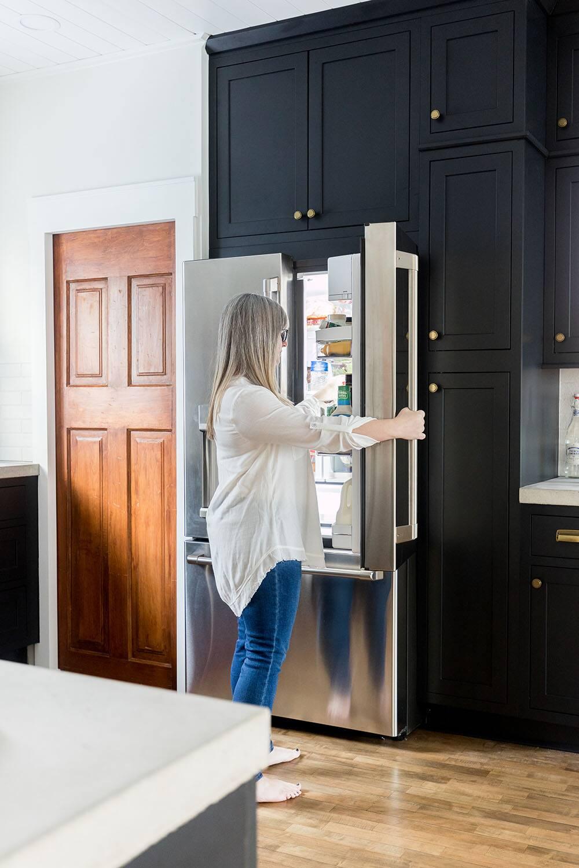 A woman reaches inside a GE Cafe refrigerator.