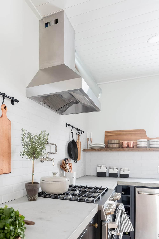 A ZLINE wall mount vent hood hangs over a gas range.
