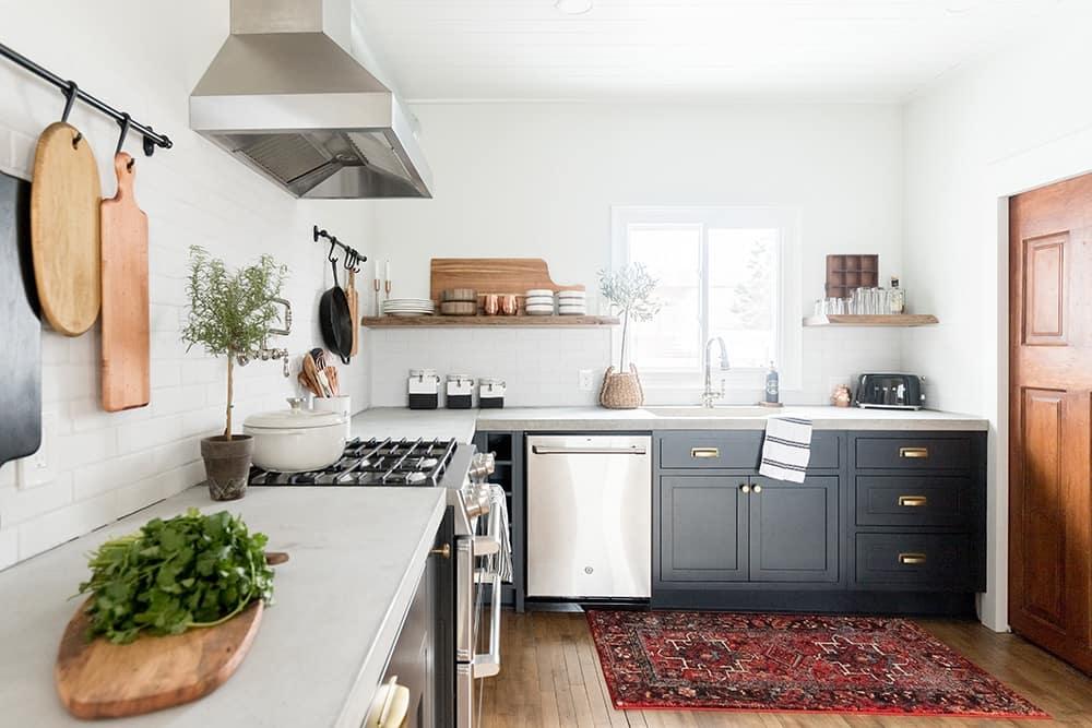 A kitchen with white tile backsplash, dark lower cabinets, and floating wood shelves.