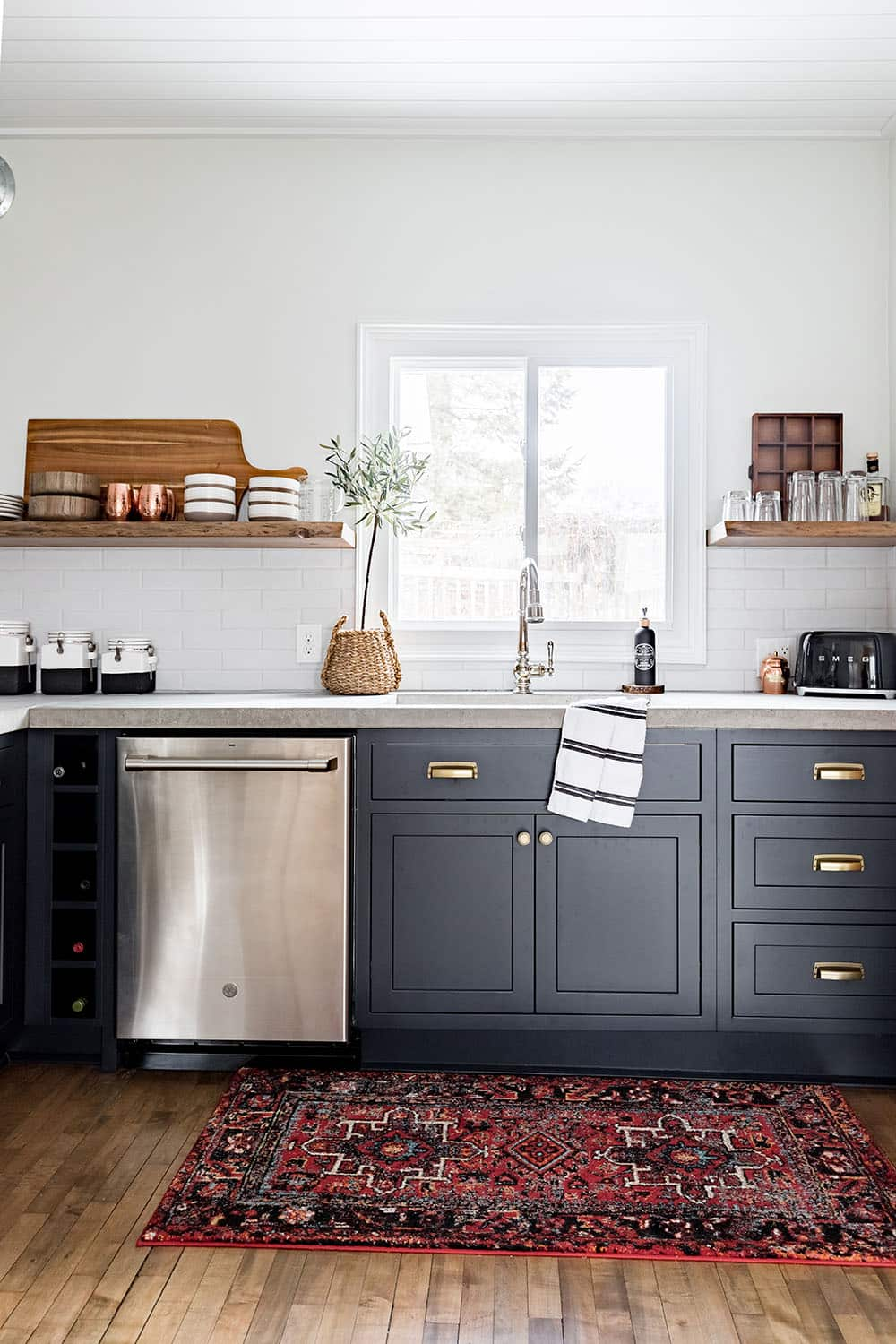 A kitchen sink area with floating wood shelves on either side.