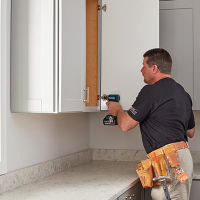 A person installing a kitchen cabinet door.