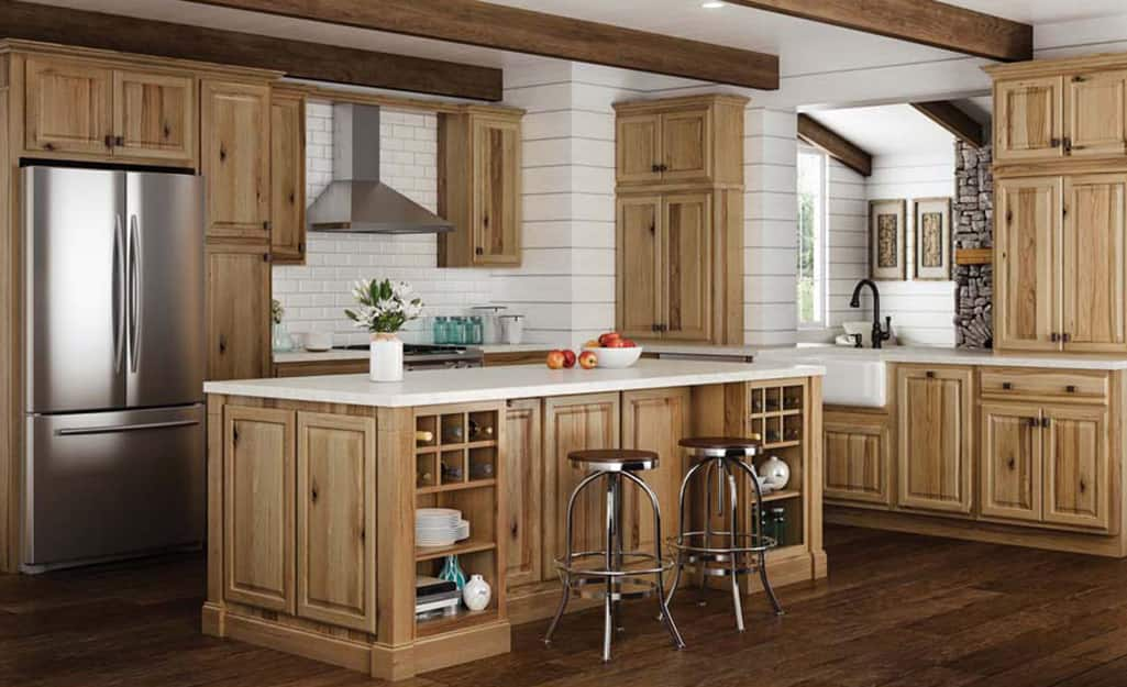 A kitchen with cabinetry in a light wood tone.