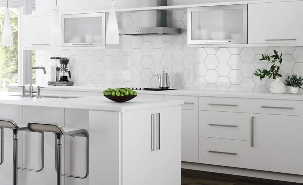 A kitchen with white cabinets that have full overlay doors.