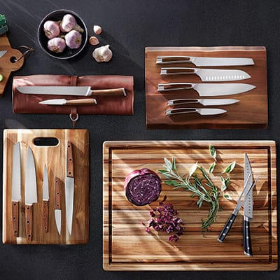 An array of kitchen knives resting on wood cutting boards.