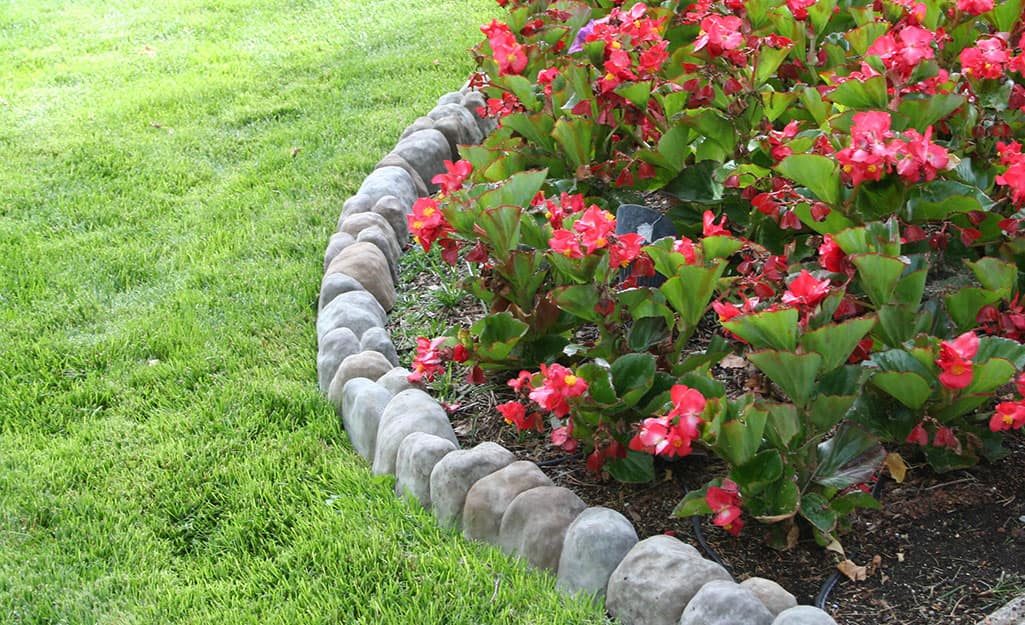Edging stones installed between a flower bed and lawn.