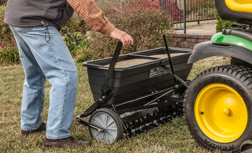 Someone using a drop spreader filled with fertilizer behind a lawn spreader.